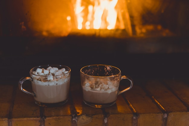 Cocoa mugs with marshmallows near the fireplace.