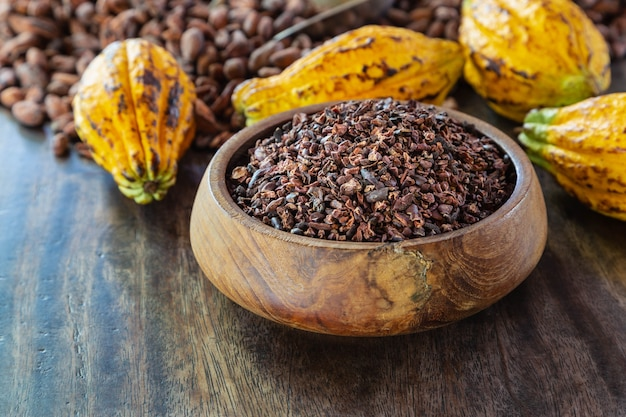 Cocoa nibs and cocoa fruit on wooden table