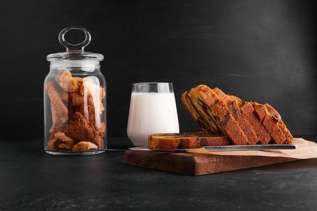 Ломтики какао-пирога на деревянной доске со стаканом молока и сухофруктов.