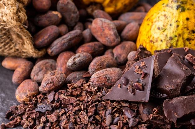 Стручки какао, бобы и порошок на деревянном столе, вид сверху