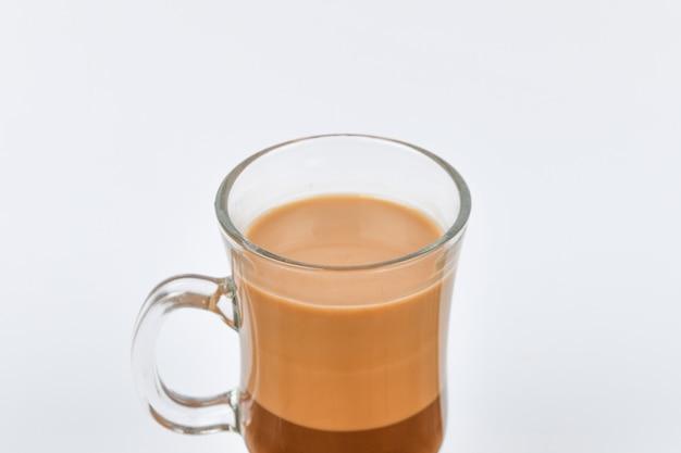 Какао наливают в стакан прозрачного стекла. какао напиток на белом.