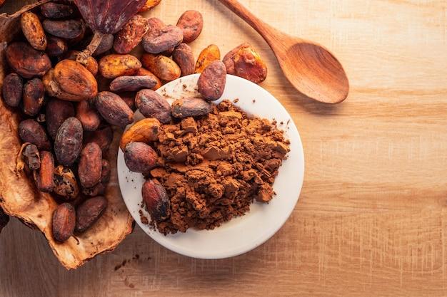 나무 배경에 코코아 포드가 있는 코코아 가루와 코코아 콩.