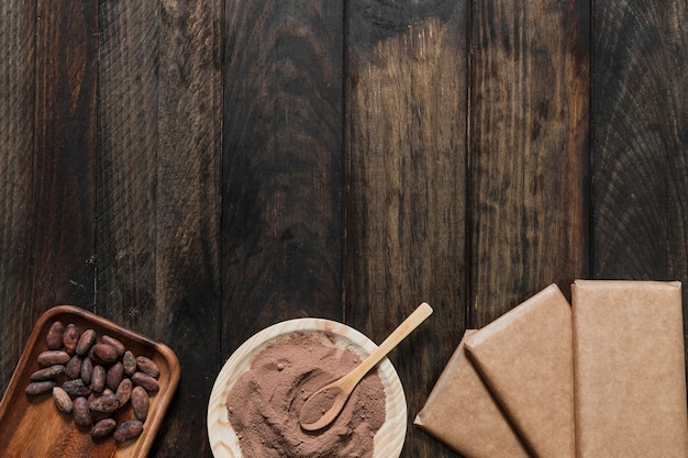 Cocoa powder and beans with wrapped chocolate bar on wooden table