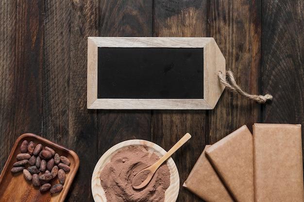 ココアパウダー、豆、包丁チョコレートバー、木製テーブル上の小さな木製スレート