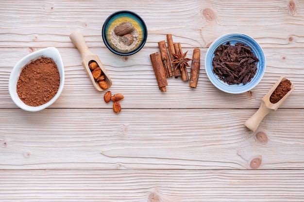 Cocoa powder and cacao beans on wooden background.