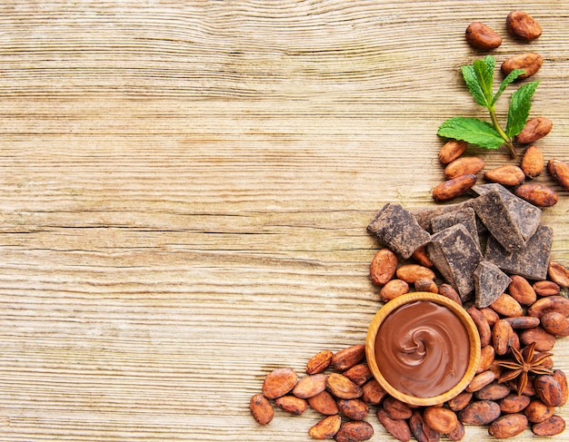 Cocoa powder chocolate and beans on wooden background