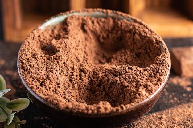 デザートを作るためのココアパウダーココアテーブルの上で食事の軽食を食べる準備ができている新鮮な部分