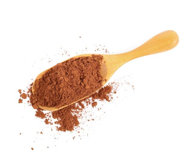 Какао-порошок в деревянной ложке, изолированные на белом фоне. вид сверху