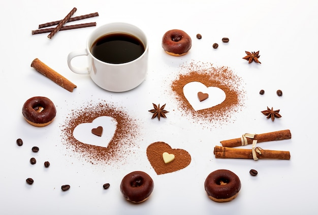 Cocoa powder in the shape of heart, mint sticks and a cup of espresso with chocolate doughnuts.