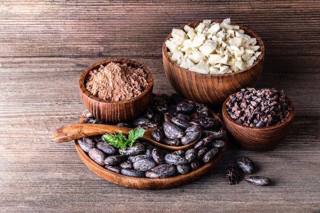 Cocoa products in wooden bowls spoon on old rustic table.