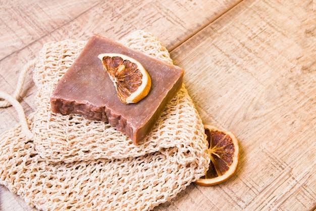 Какао-мыло из натуральных ингредиентов на трикотажной мочалке, домашнее мыло и дольки сушеного апельсина на деревянной поверхности