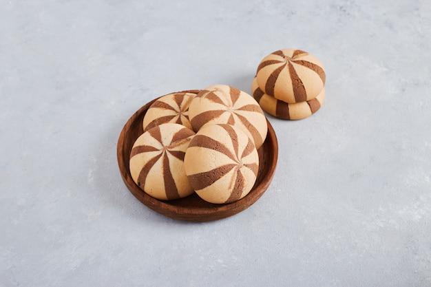 Булочки ванильного печенья какао в деревянном блюде на белой поверхности, вид сверху.