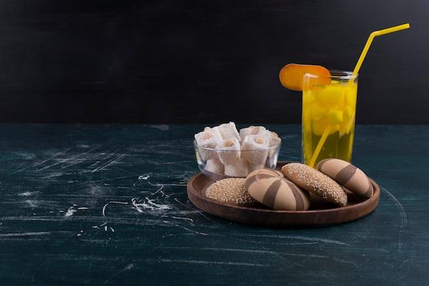 Panini biscotto al cacao e vaniglia con lokum e un bicchiere di succo in un vassoio di legno