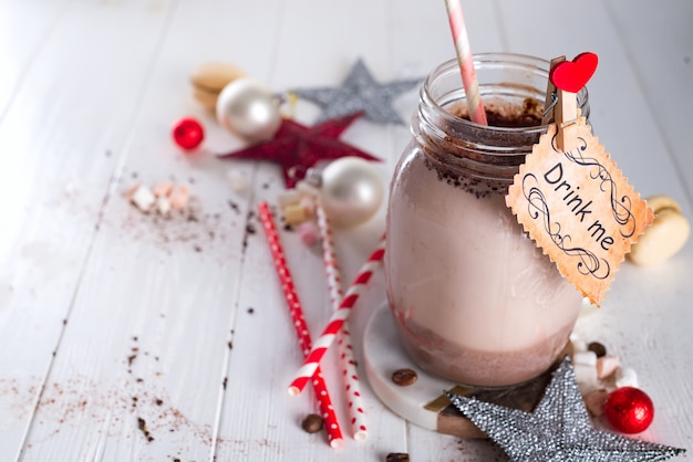 Cocoa with marshmallow and straws in the glass jar with a sign drink me
