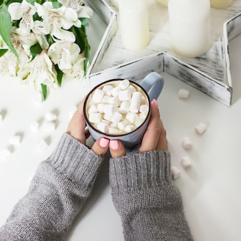 Cocoa with marshmallows in female hands on white background flowers, candles, top view