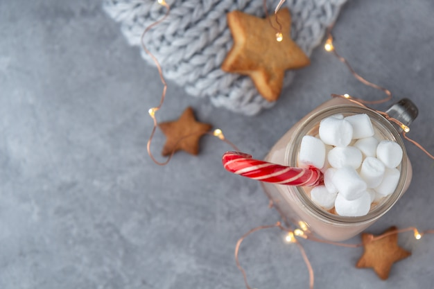 Cocoa with marshmallows and a sugar cane on a gray background with cookies and a knitted scarf with garlands.
