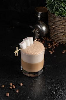 Cocoa with marshmallows in a transparent glass. a hot drink made from coffee or cocoa, with milk foam, and a decoration of three marshmallows