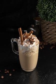 Cocoa with whipped cream, cinnamon sticks and star anise in a transparent mug.