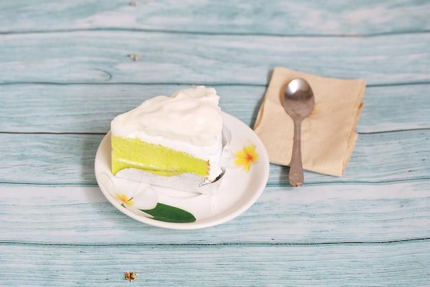 Пекарня хомадэ крем-чизкейк с кокосом на белой тарелке и поставить на деревянный стол синего цвета