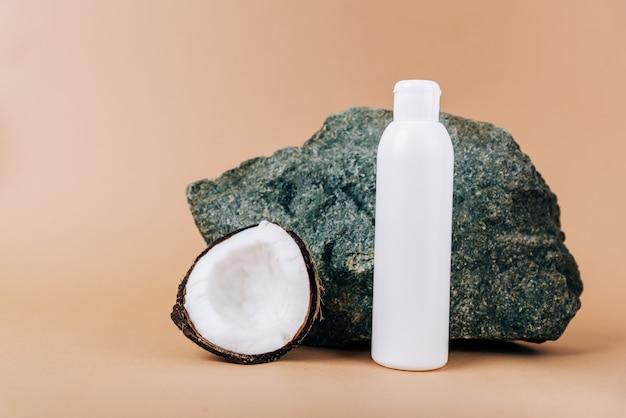 ココナッツと石の背景に化粧品のチューブ