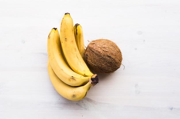木の背景にココナッツとバナナ