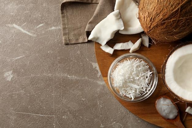 灰色のテーブルの上のココナッツとココナッツフレーク