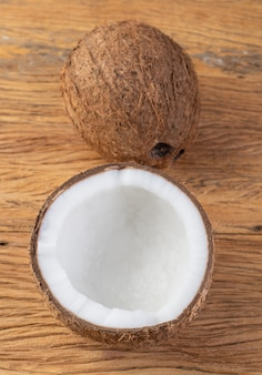 ココナッツとひびの入った半分の果物を木製のテーブルの上に置きます。