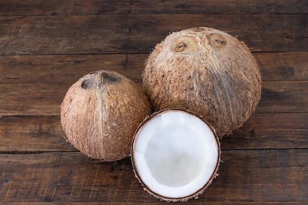 ココナッツと木製の机の上の半分のココナッツ