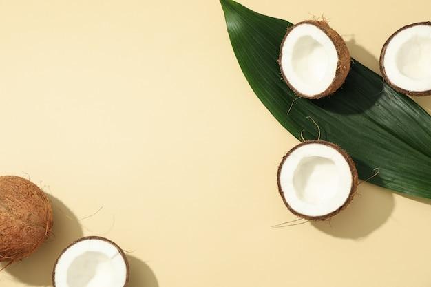 코코넛과 베이지 색 테이블에 잎입니다. 열대 과일