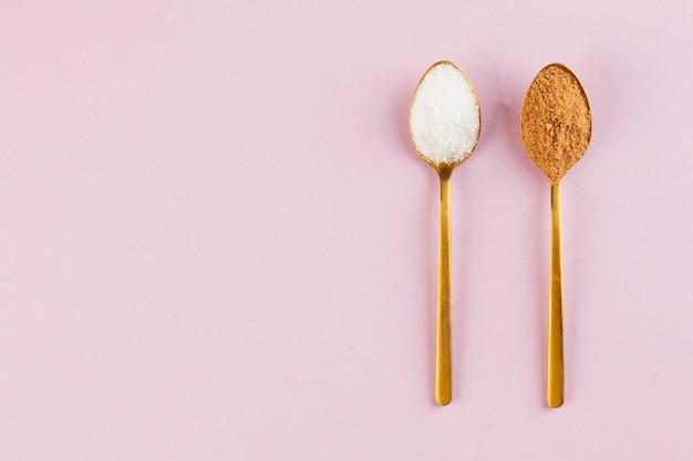 ピンクの表面に金のスプーンでココナッツと精製された白砂糖