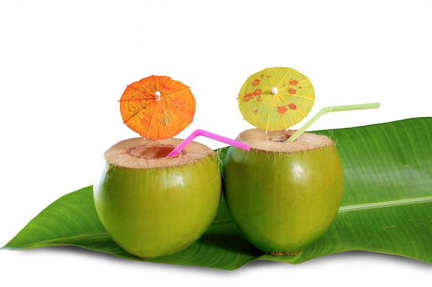 Coconut beverage straw cocktail on banana tree leaf