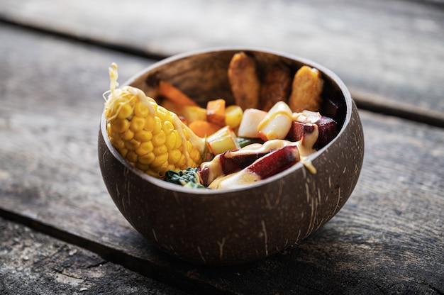 다양한 채식 음식을 제공하는 균형 잡힌 유기농 식사로 가득한 코코넛 그릇.