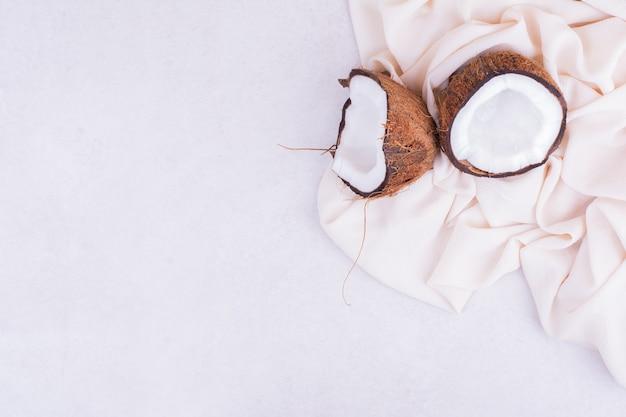 Noce di cocco spezzata in due pezzi sulla tovaglia beige