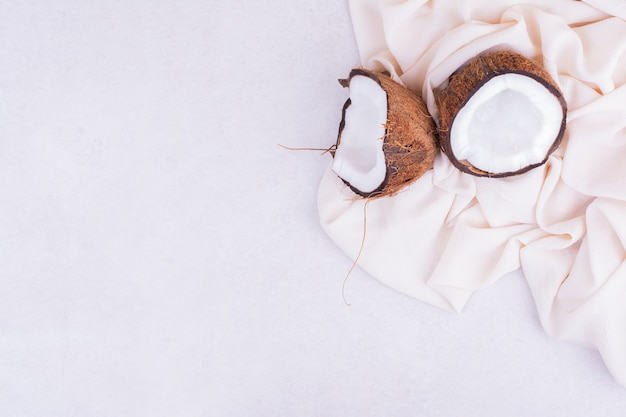 Кокос, разбитый на две части, на бежевой скатерти