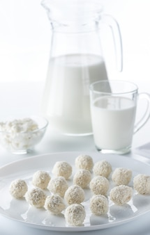 Кокосовые конфеты на фоне кувшина и чашки молока и миски творога