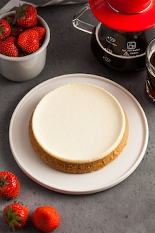 Coconut cheesecake on a round plate. taeapot with black coffee and a mug of fresh strawberries.