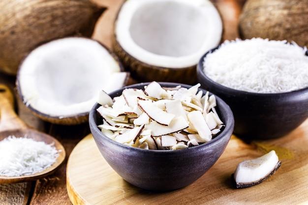 Кокосовая стружка, стружка и кусочки кокоса в глиняной миске на фоне множества спелых кокосов