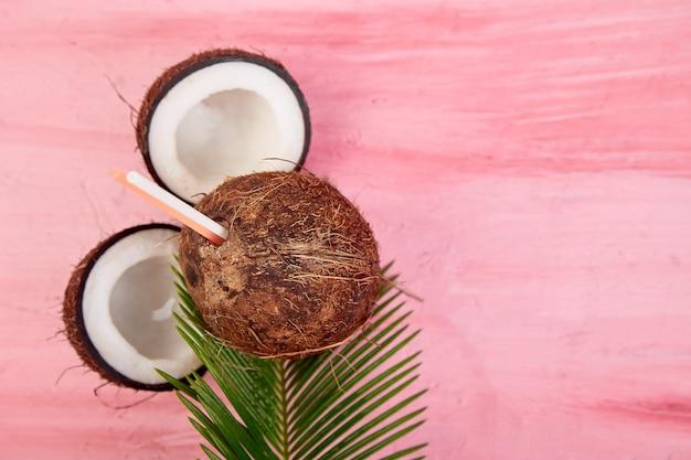 Кокосовый коктейль. летний отпуск напиток на розовом фоне