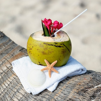 Кокосовый коктейль с соломинкой на пальме на пляже