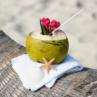 Cocktail di cocco con cannuccia su una palma in spiaggia