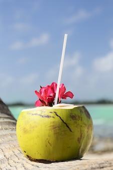 ビーチで花とココナッツカクテル