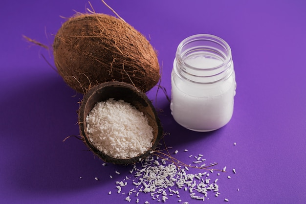 Coconut, coco flakes and coconut oil in jar on purple background. healthy cooking concept