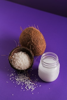 Coconut, coco flakes and coconut oil in jar on purple
