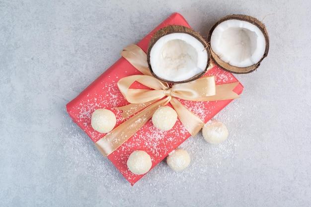 회색 테이블에 코코넛 쿠키, 코코넛 및 선물 상자. 고품질 사진