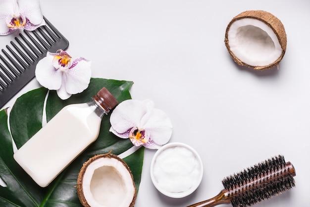 코코넛 화장품과 열대 잎. 천연 모발 관리 개념입니다.