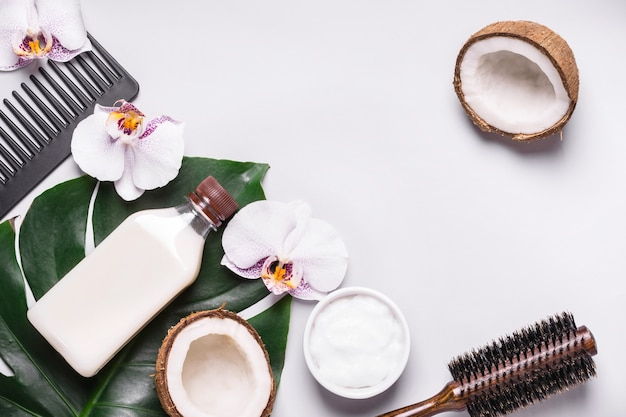 Coconut cosmetic product and tropical leaves. natural hair care concept.