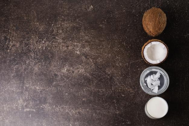 Кокос, сливки, кокосовое молоко и масло на темном фоне мрамора. экзотический крупный орех. личная гигиена. спа процедуры