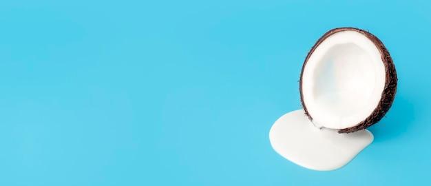 Кокосовый крем или масло со свежими кокосами на синем фоне баннера. белый сливочный сок капает из кокоса.