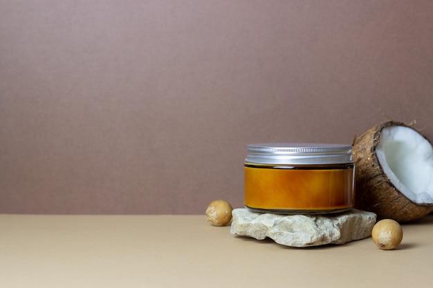 유리병에 든 코코넛 크림이나 오일과 신선한 코코넛. 천연 화장품.