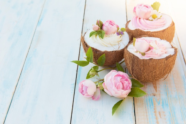 Coconut cupcakes with flowers, strawberries and cheese cream